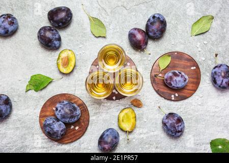 Le rakija, le raki ou le rakia est un cognac de boisson alcoolisée des Balkans à base de fruits fermentés. Prunier rakia sur la table grise Sone, vue de dessus.