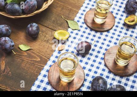 Le rakija, le raki ou le rakia est un cognac de boisson alcoolisée des Balkans à base de fruits fermentés. Rakia de prune sur une table en bois rustique.
