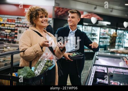 Souriez une femelle avec un assistant dans un magasin d'alimentation. Une cliente heureuse magasiner au supermarché.