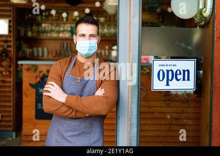 Portrait du propriétaire souriant homme portant un masque de prévention tout en se tenant à la porte de son café avec panneau ouvert.