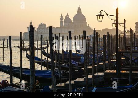 Gondole vénitienne au coucher du soleil, gondoles amarrées à Venise avec la basilique Santa Maria della Salute en arrière-plan, en Italie