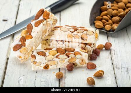 Blocs de Turron aux amandes et aux noisettes sur une table en bois rustique avec couteau et pelle
