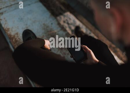 Vue de dessus des mains de dame en utilisant un smartphone tout en étant assis en métal construction à l'extérieur