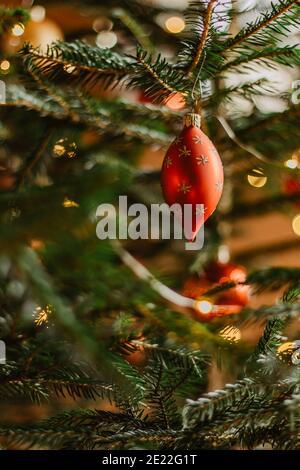 Sapin de Noël avec boule rouge brillante. Décoration de Noël festive suspendue sur un arbre flou d'arrière-plan.scène décorative traditionnelle de vacances. La veille de Noël des