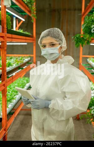 Jeune ouvrier de serre en combinaison de protection, masque, gants, lunettes et chapeau en utilisant un comprimé tout en vous regardant à l'intérieur de la ferme verticale