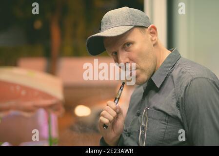Homme mûr de fumer la cigarette électronique dans les rues la nuit