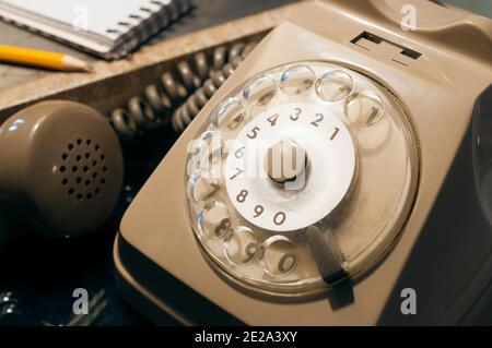 Téléphone avec disque rétro sur une table avec un crayon et un répertoire