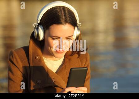 Femme satisfaite écoutant de la musique avec un casque et un téléphone portable sur la plage au coucher du soleil en hiver