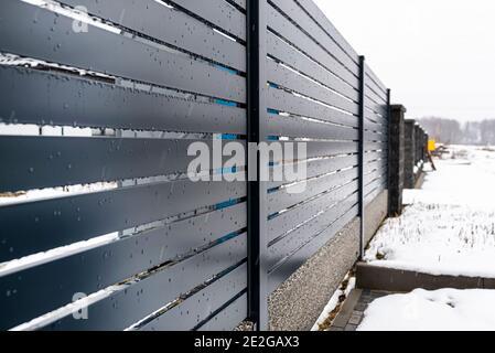 Clôture de panneau moderne anthracite, avec un connecteur de fondation de clôture visible, il pleut en hiver, en arrière-plan il y a de la neige au sol.