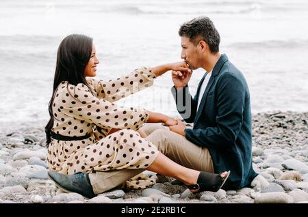 Jeune couple amoureux, homme et femme séduisant appréciant une date romantique sur la plage, homme embrassant la main de la femme