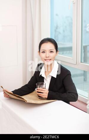 Jeune femme d'affaires tenant un journal à son bureau photo de haute qualité