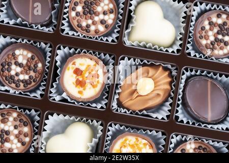 Différentes pralines au chocolat. Boîte de pralines belges de différentes formes. Assortiment de chocolats fins belges blancs, noirs et au lait