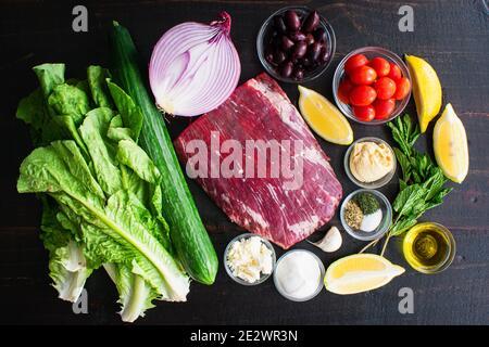 Ingrédients du Steak Bowl méditerranéen : steak de flanc cru, fruits, légumes et herbes utilisées pour faire de la salade sur fond de bois sombre