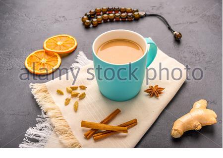 Thé Chai de masala. Boisson chaude traditionnelle indienne avec lait et épices sur serviette sur fond de pierre sombre avec ingrédients. Gros plan