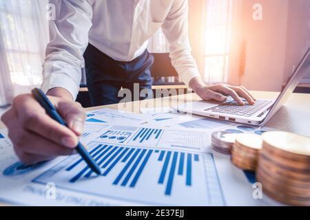Le comptable ou l'expert financier d'un homme d'affaires analyse le graphique du rapport d'affaires et le graphique financier au bureau de l'entreprise. Concept d'économie financière, banque