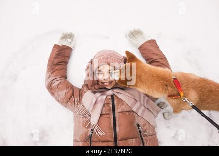 Vue de haut en bas de jolie fille couché dans la neige et de faire des anges de neige avec le chien léchant son visage tout en appréciant l'hiver dehors, copier l'espace