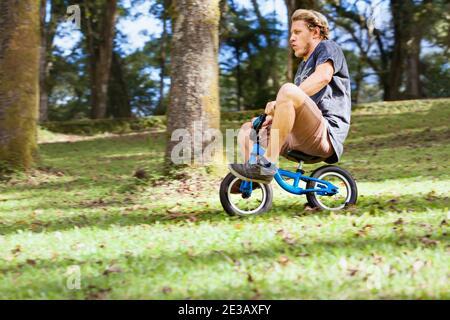 Descente amusante sur le vélo d'équilibre pour les petits enfants. Jeune homme fou qui descend d'une colline.