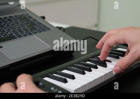 Mains jouant le piano électronique devant l'ordinateur portable. Apprendre à jouer du piano.