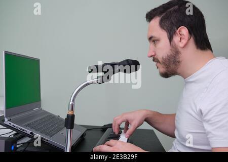 Un homme apprenant à jouer du piano électronique sur Internet à la maison. Écran vert sur l'ordinateur portable.
