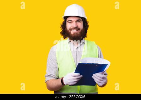Portrait d'un jeune architecte élégant tenant le travail de papier entre les mains et regardant l'appareil photo.