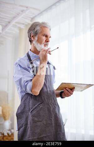 l'artiste est en train de dessiner sur toile de chevalet, l'homme gris senior aux cheveux en tablier profiter du processus de peinture, dans la salle de lumière. Banque D'Images