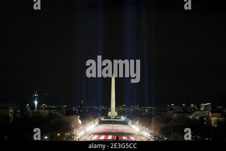 Les projecteurs éclairent le ciel depuis le « champ des drapeaux » du centre commercial national américain en l'honneur de l'inauguration prochaine du président élu des États-Unis, Joe Biden, à Washington, aux États-Unis, le 18 janvier 2021. REUTERS/Jim Bourg