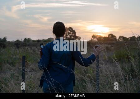 une fille regardant le coucher du soleil et buvant son compagnon dans la campagne