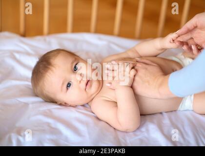 Mère massant son joli petit corps de bébé Banque D'Images