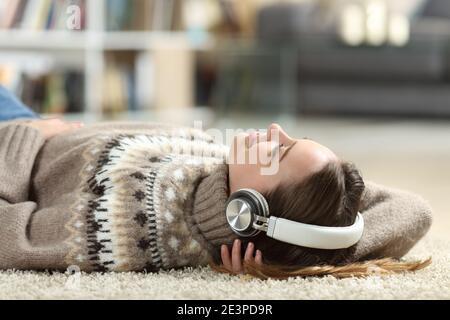 Un adolescent détendu qui écoute de la musique avec un casque couché à la maison en hiver