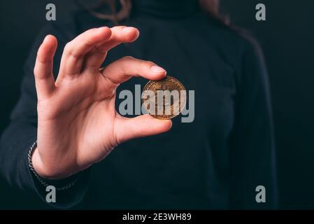 Les mains des femmes tiennent une pièce de monnaie en bitcoin sur fond noir.