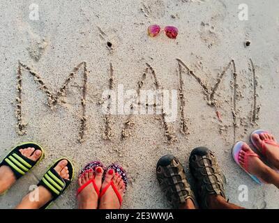 Sur la plage, le sable, les sandales s'écrivent sur le sable Banque D'Images