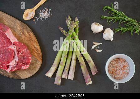 Asperges crues, romarin, steak cru, ail et sel de mer sur béton, fond de pierre. Concept de Flat Lay, vue de dessus. Alimentation saine et biologique.