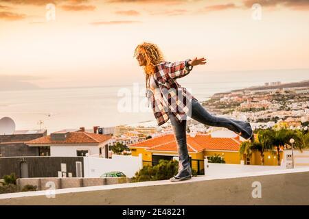 Concept de bonheur et de liberté pour une jeune femme indépendante et belle marchant équilibré sur un mur avec la ville et la côte de mer dedans contexte - vacances d'été