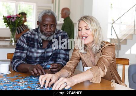 Femme caucasienne senior et homme afro-américain assis à table faire des puzzles à la maison Banque D'Images