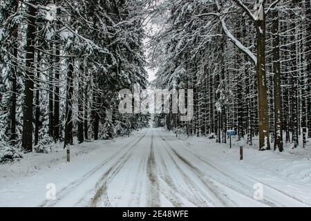 Route dangereuse recouverte de neige et de glace.route enneigée à travers la forêt.Panorama hivernal.conduite dans un paysage gelé.mauvaises conditions météorologiques.