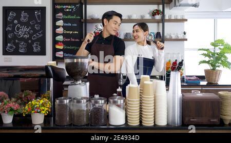 Le commerçant et le barista tiennent les porte-filtres Espresso machine avec un sourire. Ambiance matinale dans un café.