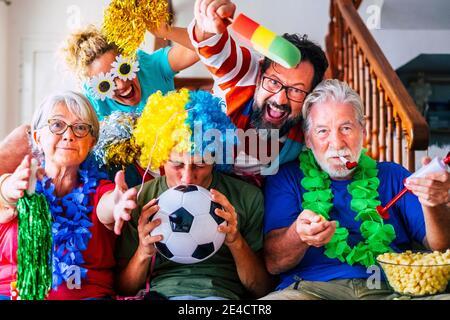 Groupe de supporters de football fous et colorés fêtent et exultent pendant le match - âges mixtes de la famille des caucasiens et les amis aiment l'activité de soutien de sport ensemble en s'amusant et allez à la victoire de l'équipe