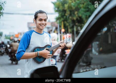 busker utilise des instruments de musique et chante devant le voiture lorsque le trafic est occupé aux feux de signalisation carrefour