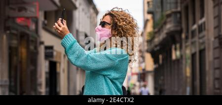 Femme faire appel vidéo de téléphone portant un masque de protection médicale pour coronavirus covid-19 urgence sanitaire dans la ville - les gens marchent et profitez de la ville protégée contre le virus de la contagion