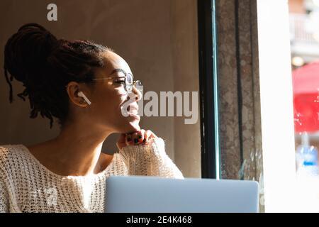 Jeune femme souriante regardant par la fenêtre tout en étant assise avec un ordinateur portable au café