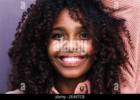 Bonne jeune femme afro avec des cheveux bouclés contre le mur