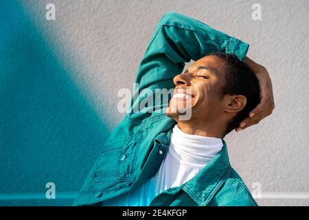 Homme souriant en se tenant les yeux fermés contre multicolore mur