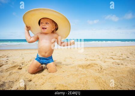 Bon petit garçon s'asseoir sur la plage avec grand chapeau de paille sur fond de mer Banque D'Images