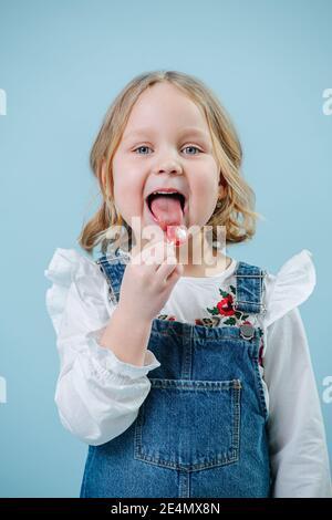 Bonne petite fille blonde aime manger des bonbon de Lollipop sur bleu