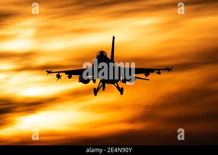 Un avion de chasse F-16 de l'armée de l'air belge est prêt à atterrir pendant un beau coucher de soleil.