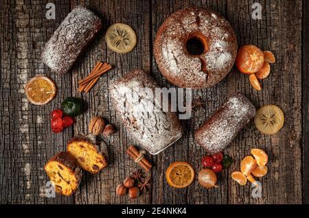 Composition de Noël de fruits secs et de stollen, avec de la mandarine, sur une table texturée en bois, avec des épices. À Noël.