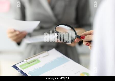 La main femelle tient une loupe et un presse-papiers avec des chiffres financiers