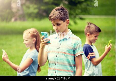 Les enfants avec les smartphones joue une partie en parc d'été