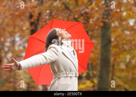 Bonne femme d'âge moyen respirant de l'air frais en hiver avec parapluie dans un parc