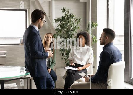 Divers collègues sont assis en cercle, à l'écoute du chef d'équipe